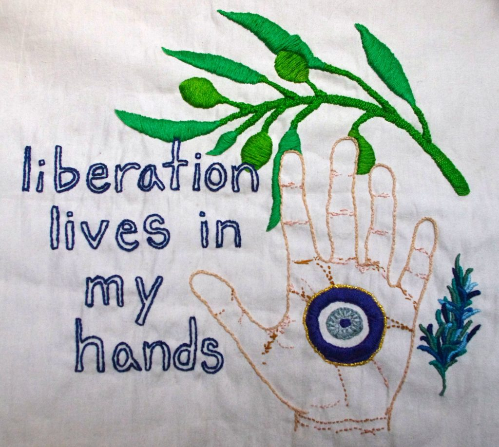 """Royal blue, lowercase text that reads """"liberation lives in my hands"""" is embroidered onto cream colored fabric. To the right of the text is an upright open hand embroidered in different shades of brown and pink. A large blue eye is stitched into the palm of the hand, known as mati, nazar and/or Khamsa. To the right of the hand is a small rosemary branch embroidered in greens and blues. A bright green olive branch is stitched into an arch above the text, Khamsa and rosemary."""